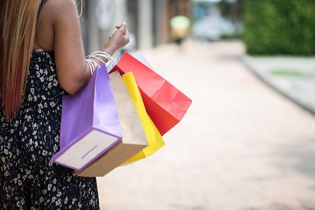 Portrait der jungen glücklichen lächelnden frau mit den einkaufstaschen, die in straße gehen