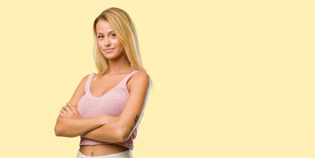 Portrait der jungen hübschen blondine, die seine arme kreuzen, lächeln und glücklich
