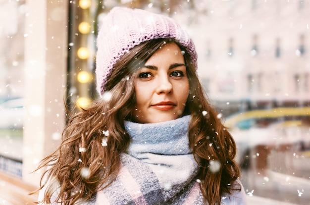 Portrait der jungen schönen frau im mantel und im hut, die die fi enjoing sind