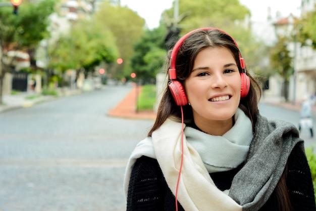 Portrait der jungen schönen frau mit hörender musik der roten kopfhörer
