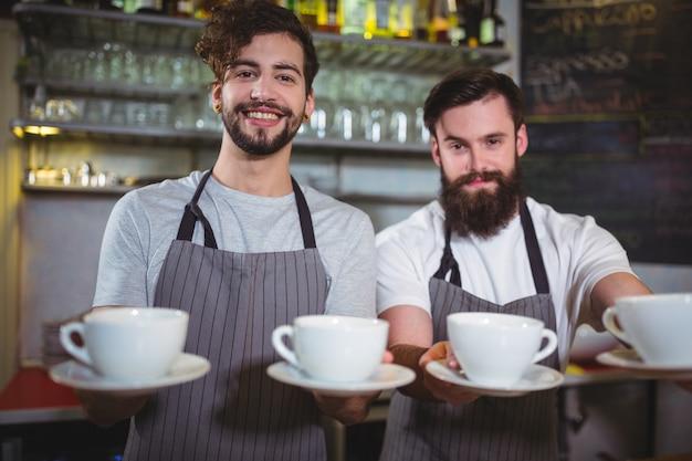 Portrait der kellner eine tasse kaffee an der theke dient,