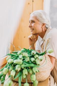 Portrait der lächelnden älteren frau mit korb der tulpen