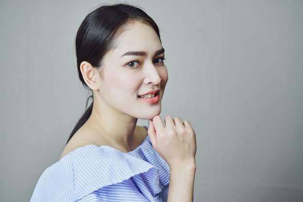 Portrait der lächelnden asiatischen jungen frauen. auf einem grauen hintergrund gibt ein weiches licht.