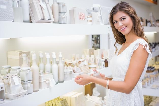 Portrait der lächelnden frau parfum prüfend