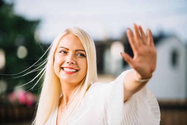 Portrait der lächelnden jungen frau, die ihre hand zeigt