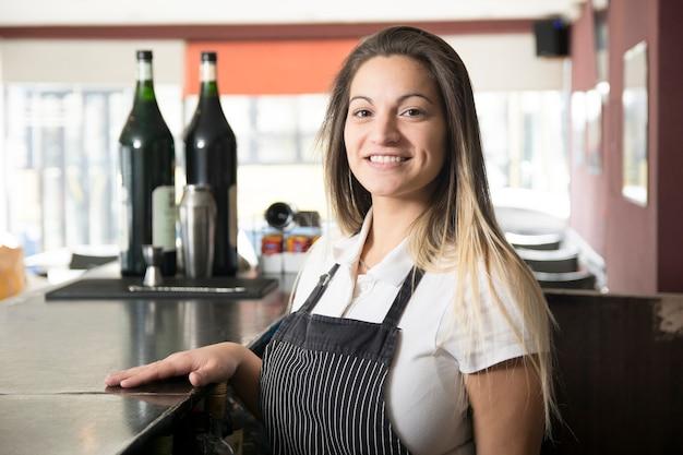 Portrait der lächelnden jungen kellnerin in der bar