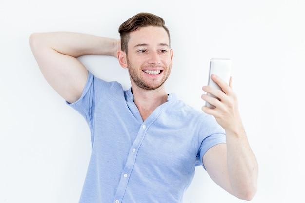 Portrait der lächelnden jungen mann posiert für selfie