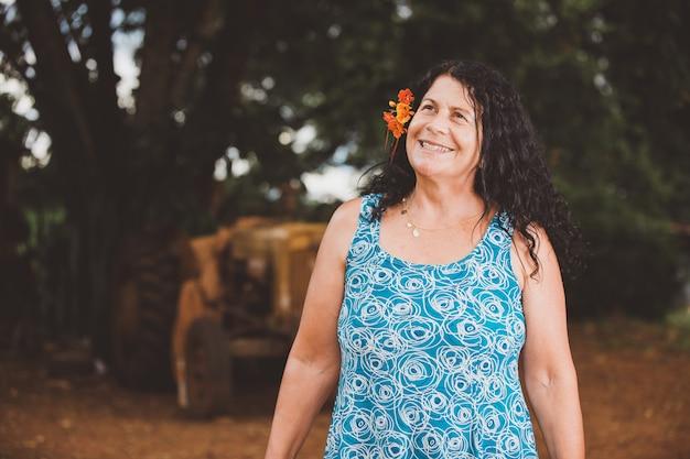 Portrait der lächelnden schönen frau in der natur mit blume auf ihrem haar