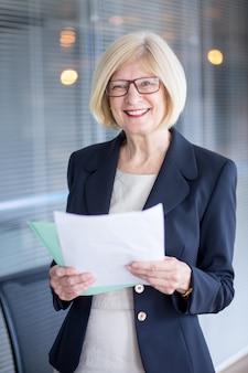 Portrait der lächelnden senior sekretärin mit papieren