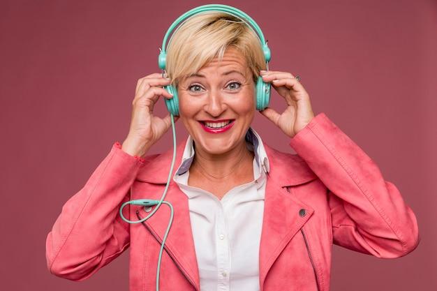 Portrait der mittleren gealterten frau mit kopfhörern