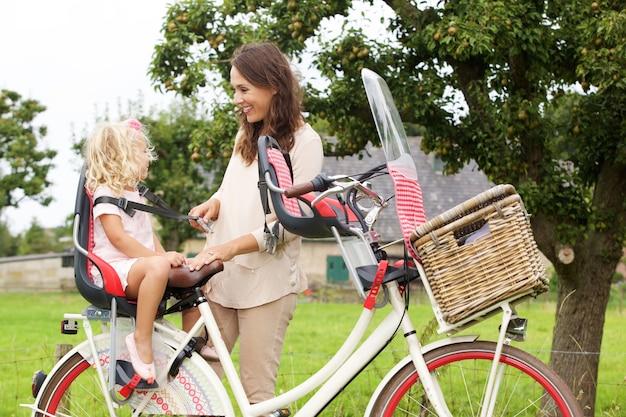 Portrait der mutter und der tochter mit fahrrad im park
