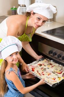 Portrait der mutter und des kindes mit pizza