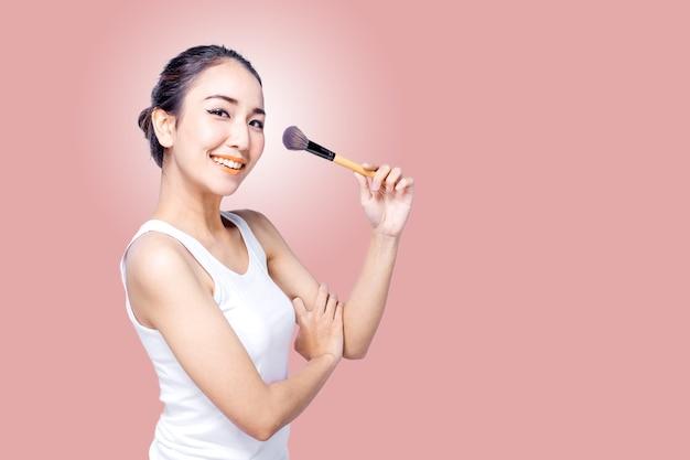 Portrait der schönen asiatischen frau mit pinsel auf rosa hintergrund