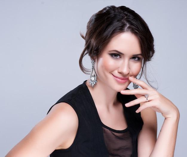 Portrait der schönen brunettefrau im schwarzen kleid. kosmetische lidschatten.