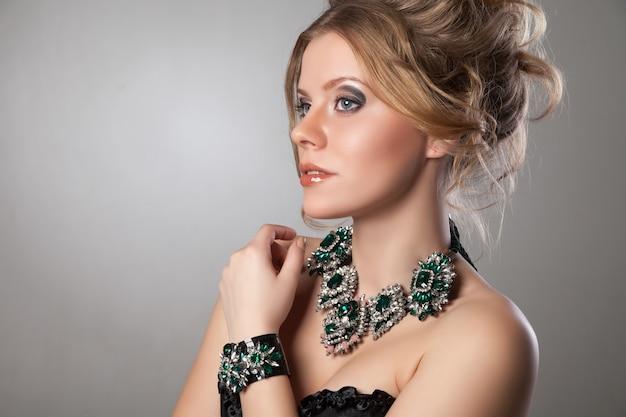 Portrait der schönen frau mit abend-make-up und großer halskette und armband. schmuck und schönheit. modefoto