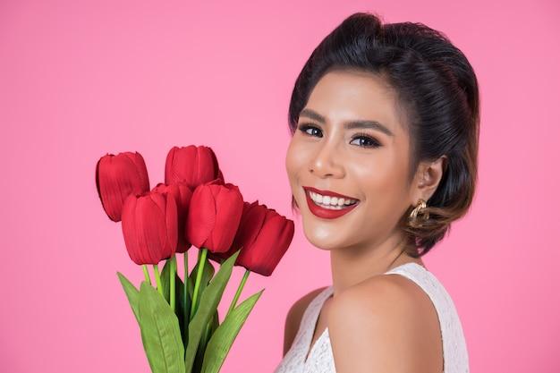 Portrait der schönen frau mit blumenstrauß der roten tulpe blüht