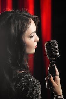 Portrait der schönen frau singend im mikrofon