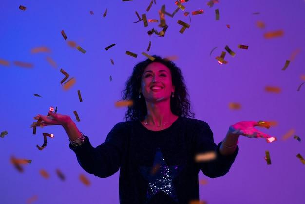 Portrait der schönen frau spielend mit confetti.