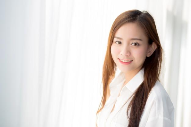 Portrait der schönen jungen asiatischen frau, die das fenster steht.