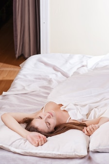 Portrait der schönen jungen frau, die im weißen bett schläft