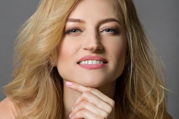 Portrait der schönen mittleren gealterten blonden frau.