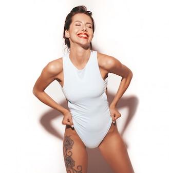 Portrait der schönen reizvollen lächelnden brunettefrau. mädchen kleidete in der blauen körperwäsche des zufälligen sommers an. modell lokalisiert auf weißem hintergrund
