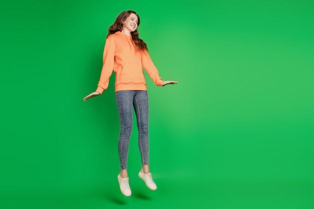 Portrait der verträumten dame springen sportlich viel spaß auf grünem hintergrund