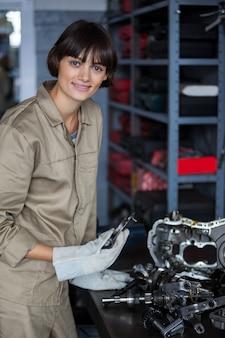 Portrait der weiblichen mechaniker arbeiten an einem autoteilen