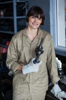 Portrait der weiblichen mechaniker hält ein auto teile
