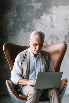 Portrait des älteren Mannes sitzend auf Stuhl unter Verwendung des Laptops