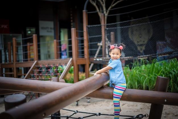 Portrait des asiatischen kleinen mädchens, das im spielplatz spielt