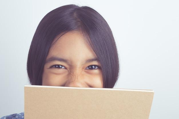 Portrait des asiatischen lächelns des kleinen mädchens, das hinter buch sich versteckt