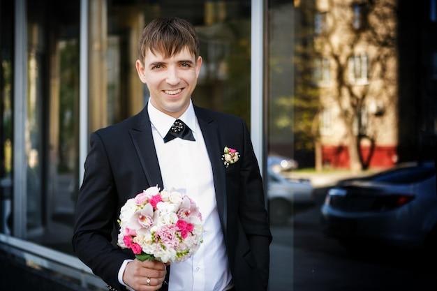 Portrait des bräutigams mit einem hochzeitsbrautblumenstrauß