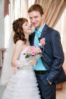 Portrait des bräutigams und der braut nahe einem fenster