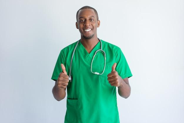 Portrait des erfolgreichen jungen doktors, der sich daumen zeigt.