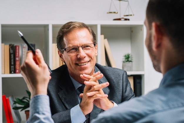 Portrait des fälligen glücklichen rechtsanwalts, der mit kunden sitzt