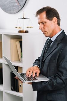 Portrait des fälligen männlichen rechtsanwaltes, der laptop verwendet