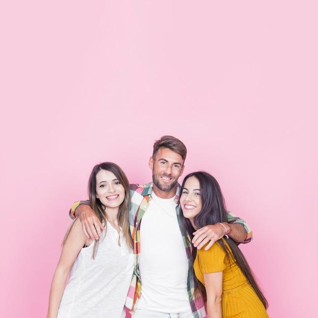 Portrait des freundlichen jungen freundes auf rosafarbenem hintergrund