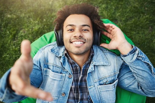 Portrait des glücklichen aufrichtigen lächelnden afroamerikanischen studenten, der auf sitzsackstuhl liegt und hand an der kamera streckt, während musik in kopfhörern hört.