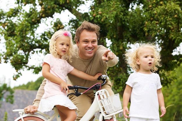 Portrait des glücklichen vaters mit zwei kleinen töchtern und fahrrad im park