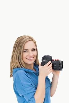 Portrait des glücklichen weiblichen fotografen mit fotographischer kamera