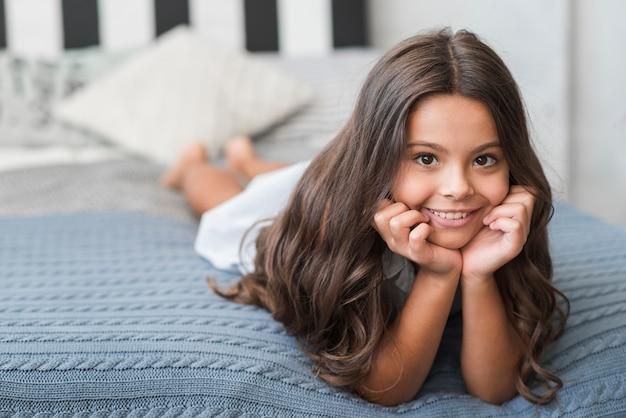 Portrait des hübschen lächelnden mädchens, das auf bett liegt