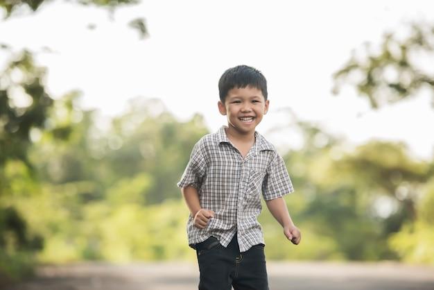 Portrait des kleinen jungen stehend im naturpark, der zur kamera lächelt.