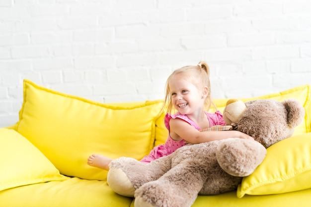 Portrait des kleinen lächelnden mädchens mit teddybären