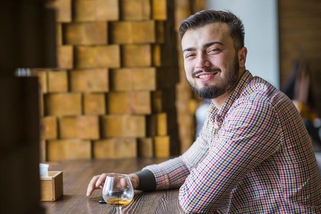 Portrait des lächelnden jungen mannes, der am restaurant sitzt