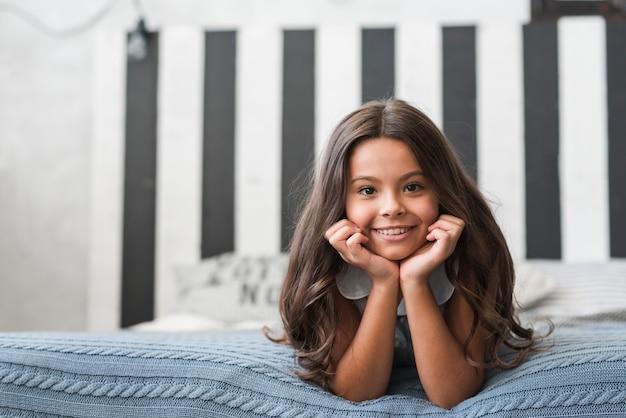 Portrait des lächelnden mädchens liegend auf bett im schlafzimmer