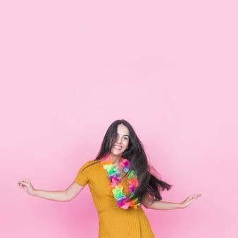 Portrait des lächelnden tanzens der jungen frau auf rosafarbenem hintergrund