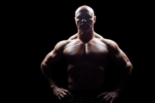 Portrait des muskulösen mannes mit den händen auf hüfte