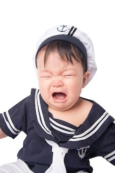 Portrait des netten kleinen asiatischen jungen 6 monate alte, die auf dem weißen bett schreien