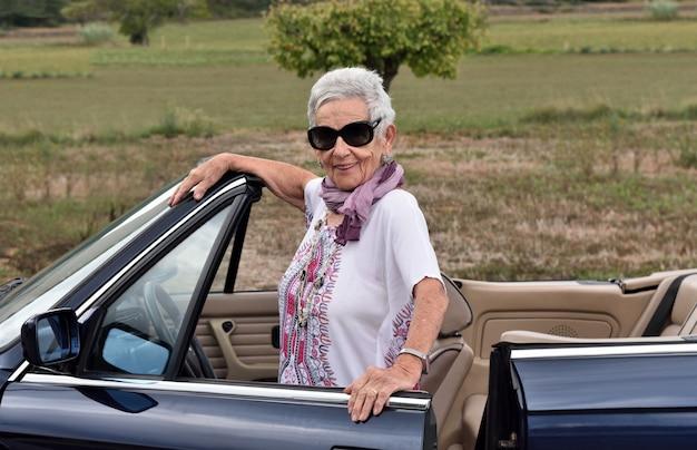 Portrait einer älteren frau mit konvertierbarem auto